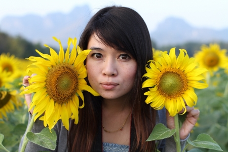 Asiatische Mädchen mit Sonnenblumen