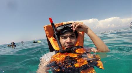 Junger Mann mit einem Rettungsweste und Schnorchel auf dem Meer.