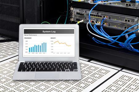 remote communication: Laptop in network data center, server room. Using for monitoring server computer performance. Stock Photo