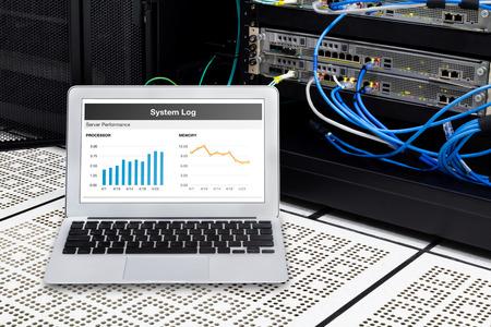 workstation: Laptop in network data center, server room. Using for monitoring server computer performance. Stock Photo