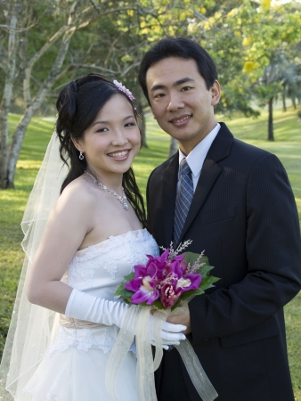 asian bride: Wedding couple holding flower bouquet smiling in the park
