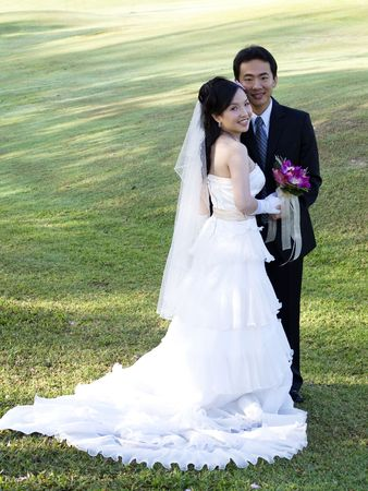 asian bride: Wedding couple holding flower bouquet smiling in the golf course Stock Photo