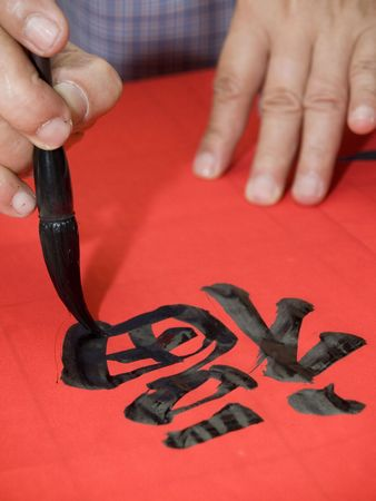 Man writing Chinese calligraphy on red paper