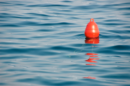 Buoy at sea. A buoy is a floating device that can have many purposes. Stock Photo