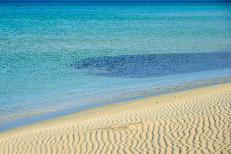 Sands on the beach. A beach is a landform along a body of water. It is usually composed of loose particles, which are often composed of rock, such as sand, gravel, shingle, pebbles. Stock Photo