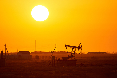 Pumpjack on sunset background. A pumpjack is the overground drive for a reciprocating piston pump in an oil well. The arrangement is commonly used for oil wells. Pumpjacks are common in oil-rich areas.