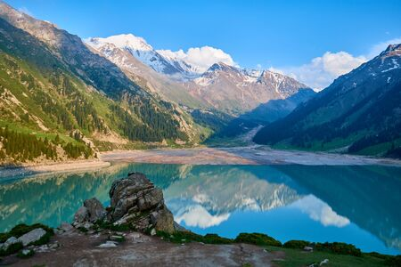 Big Almaty Lake. Blue freshwater lake. Blurred water effect. Lake with turquoise water surrounded by a mountains. Ile-Alatau National Park. Kazakhstan.