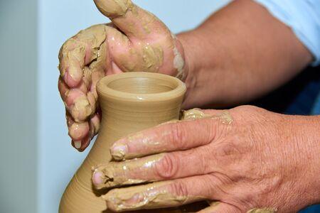 Hands of a potter. Potter making ceramic vase on the pottery wheel.