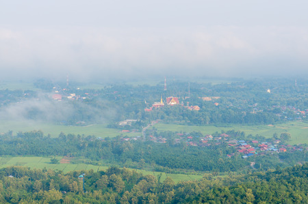 early fog: Wat Phra That Cho Hae with Fog on early morning Looking from Wat Pra That Doi Leng View Point at Phrae Province, Thailand. Stock Photo