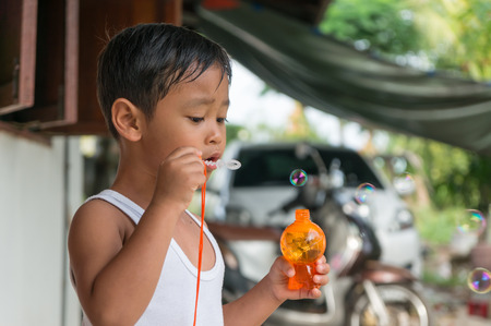dress blowing in the wind: Children playing with soap bubbles, Boy with Bubbles