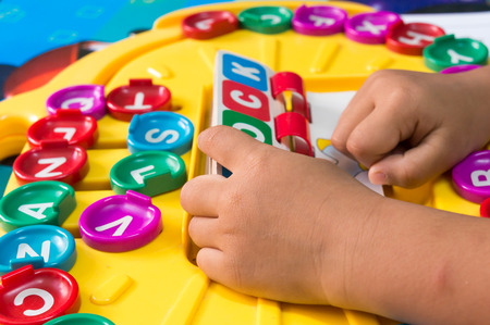 De hand van kinderen om alfabetspelen te spelen, Selectieve nadruk aan Alfabet Stockfoto