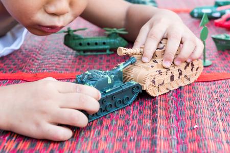 tanque de guerra: Mano de los ni�os a jugar juguete del tanque, el tanque de enfoque selectivo Foto de archivo