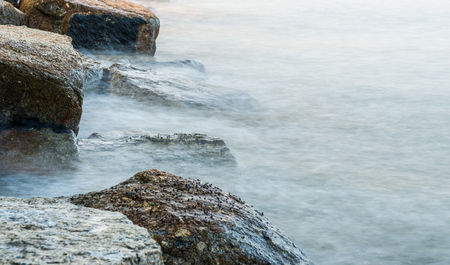 waves hits rocks. Image taken with slow shutter to show the waves motion. image may contain soft focus and blur.