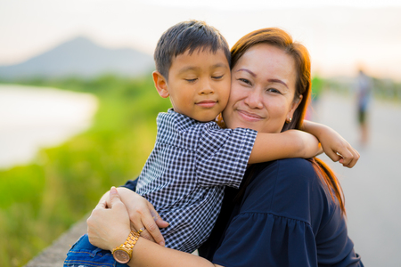 Asian mom hug her young son lovingly at sunset with nature background