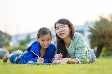Asian teenage girl teach the boy lovingly and fun in the green meadows Stockfoto - 95985174