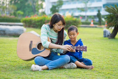 Asian teenage girl teach guitar for the boy with lovingly and fun in the green meadows Stockfoto - 96042933