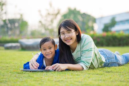 Asian teenage girl teach the boy lovingly and fun in the green meadows Stockfoto - 100437362