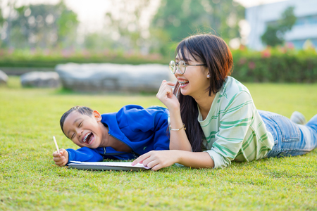 Asian teenage girl teach the boy lovingly and fun in the green meadows , the boy is blur  or out focus. Stockfoto - 107199731