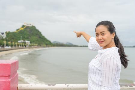 asian woman is  pointing ot  Thammikaram Temple at Khao Chong Krachok