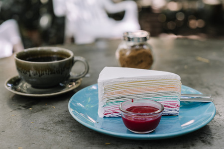 Rainbow crepe cake with strawberry jam on blue plate pastel color