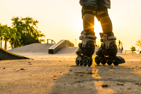 The boy rollerblading in public park with protection equipment on the sunset background