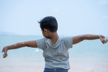 little kid boy stand on beach and  stretch oneself Imagens