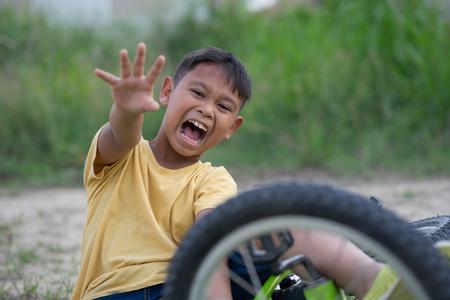 asiatischer Junge hat einen Unfall beim Fahrradfahren