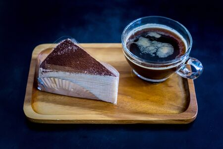 chocolate cake crepes with coffee on a wooden plate Stockfoto