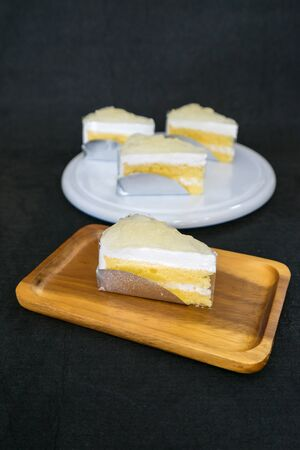 Cream cake with Toddy Palm topping on wooden plate