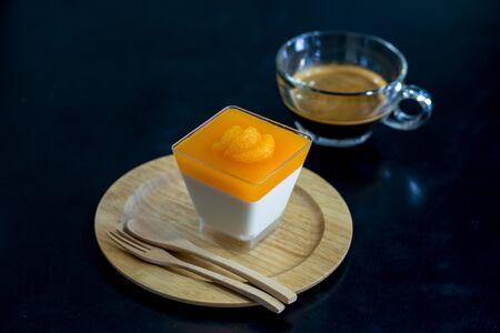 orange panna cotta on  wooden dish with black background