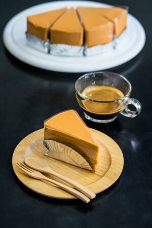 Tea cake on wooden plate with black background Stockfoto