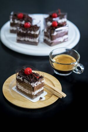 Black Forest, Chocolate cake on wooden dish with black background