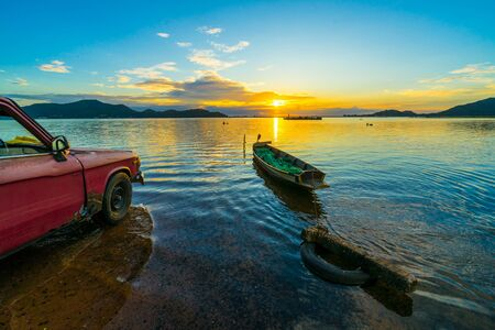 Old pickup truck parked on the waterfront with sunset at Bang phra reservoir ,sriracha chon buri,  thailand