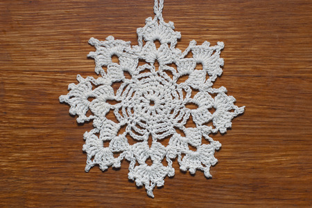 christmas motif: Crocheted snowflake  on a wooden background