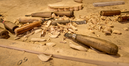 trinchante: Carving tools on table  Carver work place with the chisels and the wood chips spread all over the wooden table