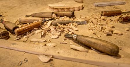 trinchante: Talla de las herramientas en la mesa de Carver lugar de trabajo con los cinceles y las astillas de madera repartidas por toda la mesa de madera