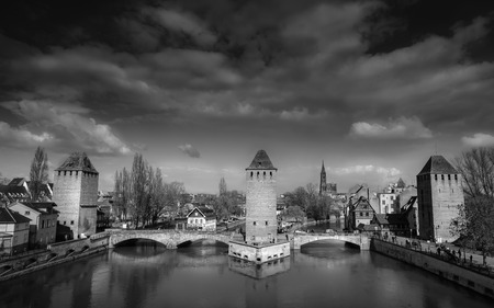 mediaval: French medieval bridges and towers  Black and white image of Les ponts couverts the covered bridges, Strasbourg, Alsace, France, with a dramatic cloudscape. Foto de archivo
