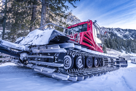 snowcat: Snow groomer car, on the side view  Side view of a snow groomer vehicle, showing details on its tracks, with aluminum-steel cleats. Snowmobile used to get ready the alpine ski slopes. Stock Photo