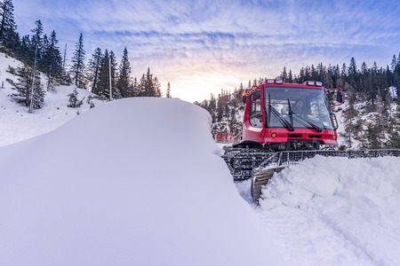 groomer: Snow groomer vehicle clearing snow off the road  Caption: Ehrwald, Austria - 12 December 2015: A man drives a snow groomer vehicle in order to clear the snow off the mountain roads from Ehrwald, Austria on 12 December 2015.