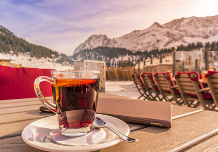 Warm drink and restaurant menu on table in alpine decor -   Image with a hot drink and a restaurant menu, on a wooden table, on a sunny winter day, mountains in the background. Picture taken in Austria.