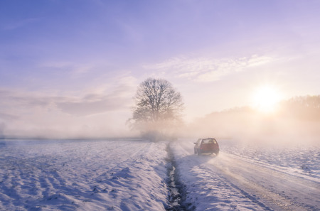 Car silhouette through fog on a winter morning - Winter image with the silhouette of a car driving on a snowy country road, through mist and the sunrise light. Stock Photo
