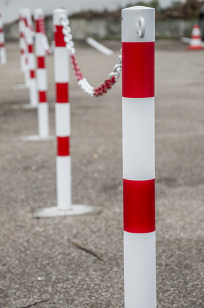 public safety: Safety chains fence  Safety fence made from more metal columns and chains, colored white and red, placed in a public parking lot.