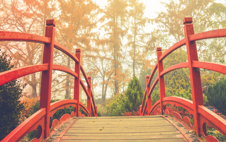 balustrades: Red wooden bridge in soft light    Wooden bridge with the red handrails in a japanese garden, against a background of autumnal trees. Stock Photo