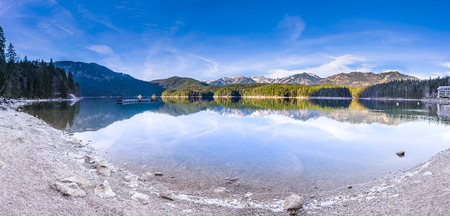 mirrored: Mountain lake in the bavarian Alps -  Alpine panorama of the lake Eibsee, located in Grainau, Germany, with the Alps mountains on the horizon and mirrored in its water.