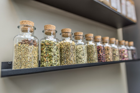 variation: Close-up image with glass bottles filled with different kinds of herbs and plants for tea, displayed on a shelf.