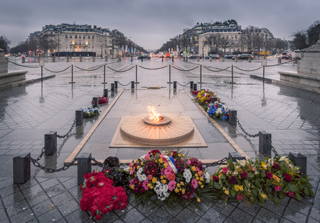 commemoration: Eternal Flame in Paris on rainy day - The Eternal flame and the monument for the unknown soldier, under the Arc de Triomphe, Paris, France