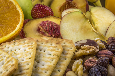 Snacks background, fruits, nuts, crackers - Mix of fresh, delicious fruits, peanuts, almonds, raisins, nuts and salty crackers, great combination  for a food background and a good idea for a healthy breakfast or snack.
