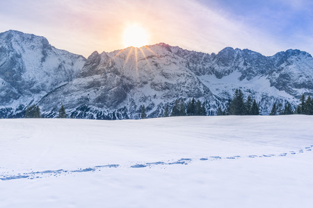 specific: Sun shining over mountain peaks and snow - Lovely winter scenery with the Austrian Alps mountains covered in snow, the trees line and a route from footsteps in the snow.