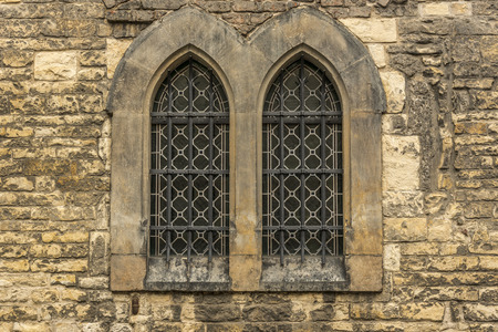 stoned: Church windows with bars  - Architectural image with two windows from an old wall stoned church. Stock Photo