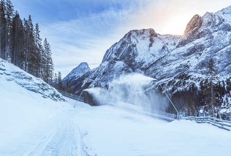 Mountain winter with snow cannons - Winter landscape with the Austrian Alps mountains and forestry road, covered in snow with the help of the snow cannons.